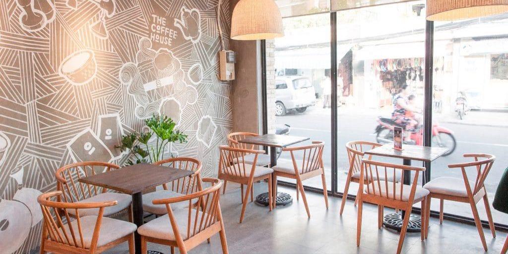 Bàn ghế gỗ tựa lưng tạo nên không gian tinh tế cho quán cafe.